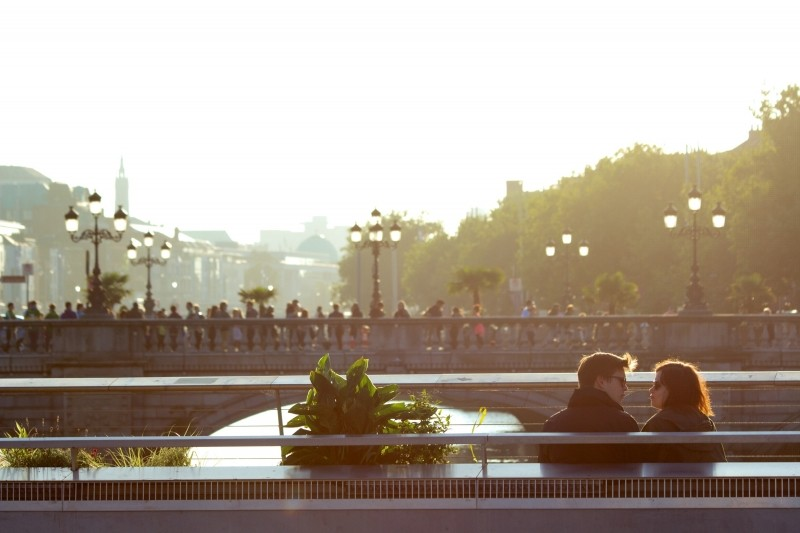 young-couple-sitting-on-bench-with-bridge-in-background